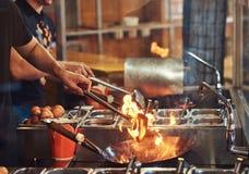 Kulinarny proces w Azjatyckiej restauraci Cook miesza warzywa w wok na płomieniu obrazy stock