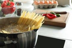Kulinarny spaghetti w garnku na elektrycznej kuchence, zbliżenie obraz royalty free