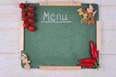 Kulinarny tło Pomidory, makaron i pusty papier na białym nieociosanym drewnianym stole, czerwonego pieprzu i Farfalle Włoski kuch Fotografia Royalty Free