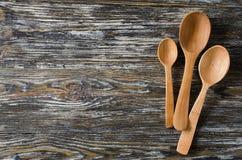 Kulinarny tło z nieociosanymi łyżkami na rocznika drewnianym stole zdjęcie royalty free