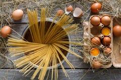 Kulinarny tło Wermiszel i jajka w kartonie, odgórny widok na nieociosanym drewnianym tle Fotografia Stock