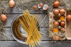 Kulinarny tło Wermiszel i jajka w kartonie, odgórny widok na nieociosanym drewnianym tle Zdjęcia Stock