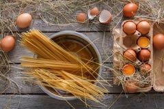 Kulinarny tło Wermiszel i jajka w kartonie, odgórny widok na nieociosanym drewnianym tle Obrazy Royalty Free