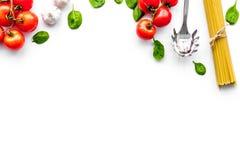 Kulinarny włoski makaron Spaghetti, pomidory, czosnek, basil i cookware na białym tło odgórnego widoku copyspace, zdjęcia royalty free