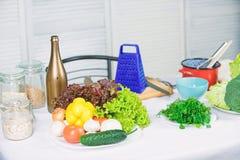 Kulinarnych warzyw po?ytecznie porady St?? z kulinarnymi naczyniami i warzywo sk?adnikami Powitanie ?wiat smaki fotografia stock