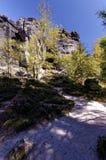 Kullar av vaggar med grönska på den mot en bakgrund av även mer högväxt steniga klippor Arkivfoton
