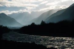 Kullar med dimmiga, regniga och rökiga områden markerade med solljus Arkivfoto