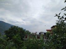 Kullar, molnigt väder och härliga liten bys hus royaltyfria foton