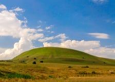 Kulle för grönt gräs och blå himmel Royaltyfri Fotografi