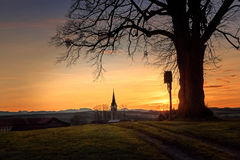 Kullen med trädet och waysiden korsar, drömlikt solnedgånglandskap Royaltyfri Foto