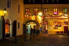 Kullerstengata och upplyst restaurang i gammal stad av Pra Royaltyfria Foton