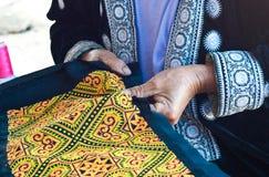 Kullestamkvinna med handen som broderas på torkduken Arkivbild