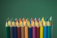 Kulöra blyertspennor på den svart tavlan Fotografering för Bildbyråer