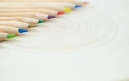 Kulöra blyertspennor på träbakgrund Royaltyfri Fotografi