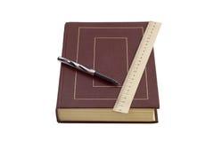 Kulspetspenna, linjal och en bok Royaltyfri Foto