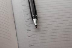 kulspetspenna på Notepadbakgrund arkivfoto
