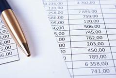 Kulspetspenna som ligger i ett hörn på utskrivavna finansiella tabeller Arkivfoton