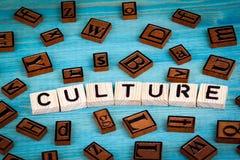 Kulturwort geschrieben auf hölzernen Block Hölzernes Alphabet auf einem blauen Hintergrund Stockbilder