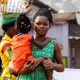 Unidentified Ghanaian woman with braids carries her baby. KUMASI, GHANA - Jan 16, 2017: Unidentified Ghanaian woman with braids carries her baby stock photography