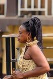 Unidentified Ghanaian woman with braids walks on the street. Pe. KUMASI, GHANA - Jan 16, 2017: Unidentified Ghanaian woman with braids walks on the street stock photography