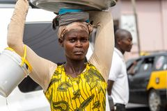 Unidentified Ghanaian woman carries a basin on her head and a b stock photo