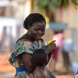 Unidentified Ghanaian woman in colored dress with braids talks. KUMASI, GHANA - Jan 16, 2017: Unidentified Ghanaian woman in colored dress with braids talks to stock photography