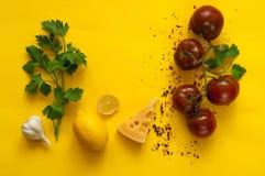 Kumato και συστατικά ντοματών για το μαγείρεμα των ζυμαρικών στο κίτρινο υπόβαθρο Το πλαίσιο φιαγμένο από οργανικά προϊόντα, διάσ στοκ εικόνα με δικαίωμα ελεύθερης χρήσης