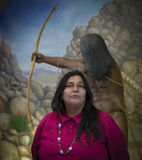 Kumeyaay Indian, Tecate, Mexico. A Kumeyaay, otherwise spelled as Kumiai, Indian woman stands in front of a figurine of Kumeyaay male hunting with bow and arrow royalty free stock image
