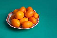 Kumquat de la placa en un fondo coloreado. Fotografía de archivo libre de regalías