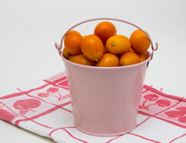 Kumquat en el cubo rosado imagenes de archivo