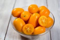 Kumquat en una placa, kumquats anaranjados orgánicos crudos, pequeñas naranjas CH Fotos de archivo