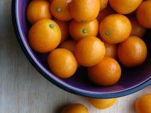 Kumquat sul bordo di taglio di legno Immagine Stock