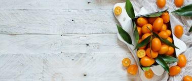 Kumquat fruits on a wooden background. Kumquat fruits in a metal box on a grey background top view stock photos