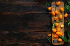 Kumquat fruits on an old wooden background. Top view royalty free stock photo