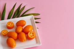 Kumquat fruits on a pink background. Kumquat fruits on a plate on a pink background royalty free stock photography