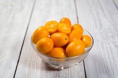 Kumquat i en platta, rå organiska orange Kumquats, små apelsiner CH Arkivfoton