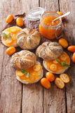 Kumquat jam in a glass jar and sweet sandwiches close-up. Vertic Royalty Free Stock Photo