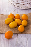 Kumquat. S on wooden background with braided basket Royalty Free Stock Photos
