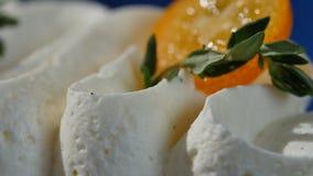 Kumquat på krämen Den orange kumquaten lokaliseras på det vita kräm- slutet upp Arkivfoton