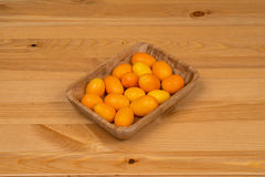 Kumquats in a bamboo bowl on a wooden surface. Kumquats in a bamboo bowl Royalty Free Stock Photos