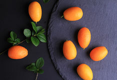 Kumquats on black background. Colorful fruits on dark background. Cooking, Healthy eating concept. Royalty Free Stock Images