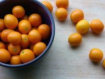 Kumquats na placa de corte de madeira Fotos de Stock Royalty Free