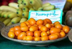 Kumquats staplar på en träplatta på försäljning med bananer i bakgrund royaltyfria foton