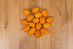 Kumquats on a wooden surface. Top view Royalty Free Stock Images