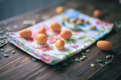 Kumquats on wooden table soraunded by pupmkin seed Stock Photography