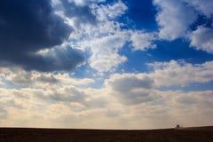 Kumuluswolken des blauen Himmels über Dunkelheit pflogen Feld Lizenzfreies Stockfoto