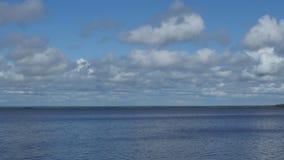 Kumuluswolken fliegen über See stock footage