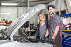 Kund för auto mekaniker och kvinnligi garage arkivfoton