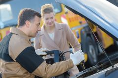 Kund för auto mekaniker och kvinnligi garage arkivfoto
