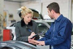 Kund f?r auto mekaniker och kvinnligi garage royaltyfri bild